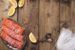 Raw salmon fillet with pepper sweetbread and salt on baking paper rustic theme with copy-space. Flat lay.  Royalty Free Stock Image
