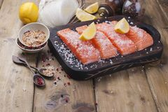 Raw salmon fillet with pepper sweetbread and salt on baking paper rustic theme with copy-space. Raw salmon fillet with pepper sweetbread and salt on baking Stock Images