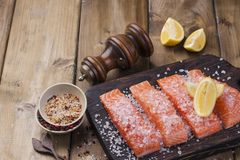 Raw salmon fillet with pepper sweetbread and salt on baking paper rustic theme with copy-space. Raw salmon fillet with pepper sweetbread and salt on baking Royalty Free Stock Photos