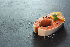 Raw salmon fillet with peppers and sea salt. Over dark stone background. Copy space Stock Photos