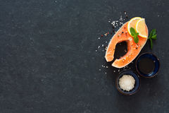 Raw salmon fillet with peppers and sea salt. Over dark stone background. Top view. Copy space Royalty Free Stock Photo