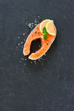 Raw salmon fillet with peppers and sea salt. Over dark stone background. Top view. Copy space Stock Images