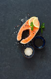 Raw salmon fillet with peppers and sea salt. Over dark stone background. Top view. Copy space Stock Photos