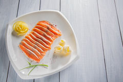 Raw salmon fillet pieces served with spices, lemon, butter and herbs on white plate and wooden table Royalty Free Stock Photos