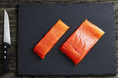 Raw salmon fillet on slate plate, top view. Raw salmon fillet on slate plate on old dark wooden table with knife, view from above, close-up Royalty Free Stock Photography