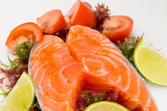 Raw salmon fillet with vegetables. On white background Royalty Free Stock Photo