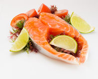 Raw salmon fillet with vegetables. On white background Stock Photography
