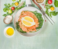 Raw salmon fillet in white Frying pan with oil, fresh seasoning,oil , spoon and fork on green rustic wooden background. Top view, place for text Stock Images