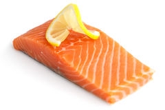 Raw salmon fillet on white. Lemon slice.  Royalty Free Stock Photo