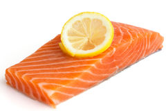 Raw salmon fillet on white. Lemon slice Royalty Free Stock Images