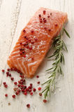 Raw salmon fillet on white rustic wood. Raw salmon fillet with coarse salt, red pepper and rosemary on rustic wooden table Stock Photography