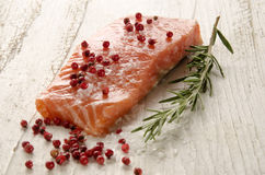 Raw salmon fillet on white rustic wood. Raw salmon fillet with coarse salt, red pepper and rosemary on rustic wooden table Stock Image