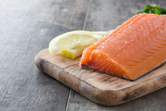 Raw salmon fillet on wooden background. Raw salmon fillet on wooden table background Royalty Free Stock Image