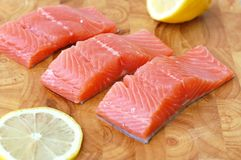 Raw salmon fillet with yellow lemon on brown wooden background. Front horizontal view Stock Images