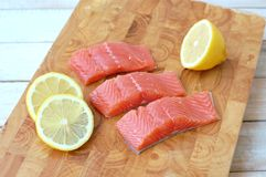 Raw salmon fillet with yellow lemon on brown wooden background. Front horizontal view Stock Photos