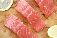 Raw salmon fillet with yellow lemon on brown wooden background. Overhead horizontal view Royalty Free Stock Images