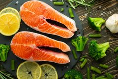 Raw salmon fillets and ingredients, vegetables for cooking on a dark background in a rustic style. Top view, flat-lay, healthy royalty free stock image