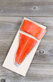 Raw Salmon Fillets placed on Grilling Plank. Vertical top view of raw red salmon, skin side down, on maple wood grilling plank with rustic wooden boards Royalty Free Stock Photo