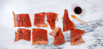 Raw salmon fillets prepared for smoke cooking on marble stone co Stock Photo