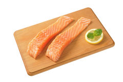 Raw salmon fillets. Two raw salmon fillets on wooden cutting board Royalty Free Stock Photos