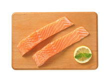 Raw salmon fillets. Two raw salmon fillets on wooden cutting board Stock Photos