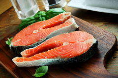 Raw salmon filllets. Two pieces of red salmon fillets placed on the wooden cutting board Royalty Free Stock Photography