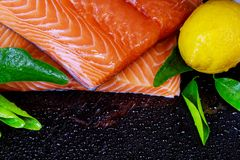 Raw salmon fish fillet on black background and lemon. Fresh raw salmon fish fillet on black background and lemon Royalty Free Stock Photos