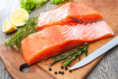 Raw salmon fish fillet with fresh herbs. On cutting board Royalty Free Stock Photography