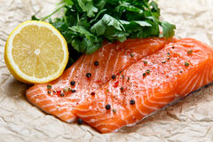 Raw Salmon fish fillet with fresh herbs on crumpled paper. Stock Photos