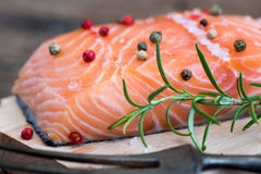 Raw Salmon Fish Fillet with Fresh Herbs. On Cutting Board ready to Cook Royalty Free Stock Photo