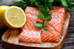 Raw Salmon fish fillet with fresh parsley on cutting board Royalty Free Stock Photos