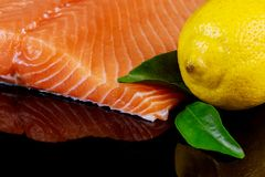 Raw salmon fish fillet on black background. Raw salmon fish fillet and lemon on black background Royalty Free Stock Photos