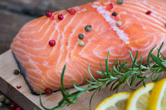 Raw Salmon Fish Fillet with Lemon and Fresh Herbs. Raw Salmon Fish Fillet with Lemon, Spices and Fresh Herbs on Cutting Board Stock Photography