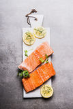 Raw Salmon fish fillet with lemon on white cutting board Stock Photos
