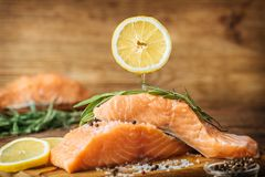 Raw salmon fish fillet on wooden background. Stock Photo
