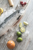 Raw salmon fish in ice and vegetables. On white table. Baking paper Stock Photos