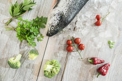 Raw salmon fish in ice and vegetables. On white table. Baking paper Stock Photo