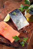 Raw Salmon Fish Meat on Cutting Board. Close up Raw Salmon Fish Meat on Wooden Cutting Board with Herbs and Spices and Olive Oil Stock Photos