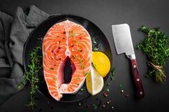 Raw salmon fish steak on dark background Stock Photography