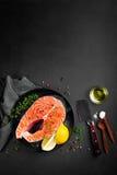 Raw salmon fish steak on dark background stock images