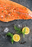 Raw salmon fish steak with ingredients like lemon, pepper, sea salt and dill on black board, modern gastronomy in restaurant Royalty Free Stock Images