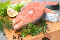 Raw salmon fish steaks. With fresh herbs on cutting board Royalty Free Stock Image