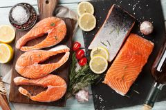 Raw salmon fish steaks and fillet. With spices cooking on cutting board. Top view Royalty Free Stock Photo