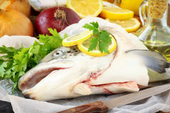 Raw salmon head. Fresh uncooked salmon head on parchment paper with the ingredients for the broth - onion, fresh parsley and lemons Royalty Free Stock Photos