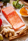 Raw salmon for a healthy heart. Raw fresh salmon rich in omega-3 fatty acids for a healthy heart and cardiovascular system with root ginger, cinnamon, broccoli Royalty Free Stock Photos