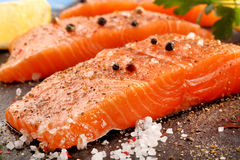 Raw salmon with herbs and spices. Ready for baking on stone background Royalty Free Stock Image
