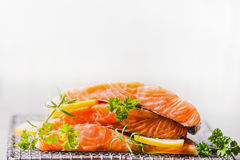 Raw salmon with lemon for tasty cooking on light background Stock Photos