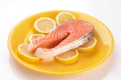 Raw salmon on lemons in yellow plate. Royalty Free Stock Images