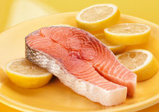 Raw salmon on lemons in yellow plate. Royalty Free Stock Photography