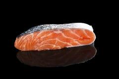 Raw salmon piece. Raw fresh salmon piece on black background. Seafood eating, minimal sparse style Stock Photos